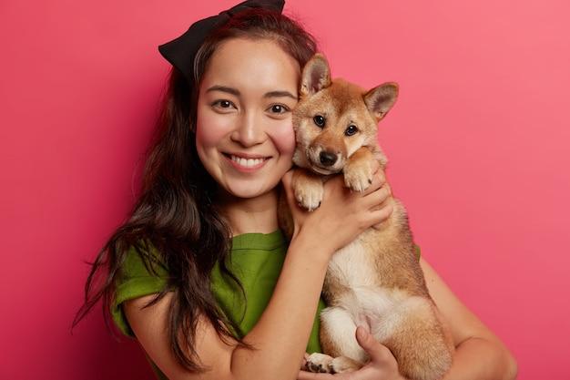 Portret van zorgzame gemengd ras vrouw houdt stamboom pup dicht bij het gezicht, omhelst shiba inu hond, veel plezier, geniet van huiselijke ontspanning, voor altijd samen zijn, chillen in de studio.