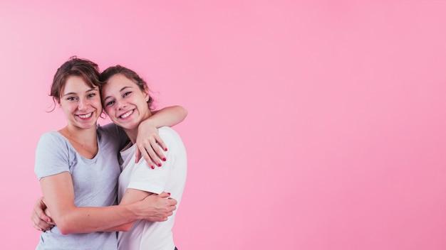 Portret van zuster die elkaar over roze achtergrond koestert