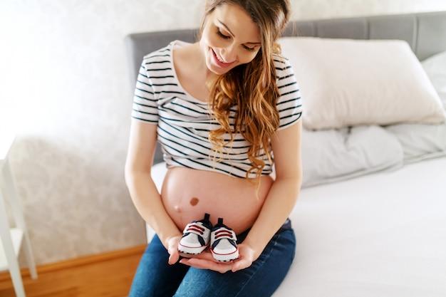 Portret van zwangere lachende mooie vrouw met babyschoenen zittend op het bed in de slaapkamer.