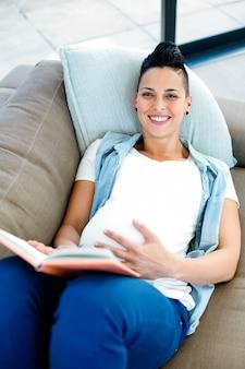 Portret van zwangere vrouw die een boek leest terwijl het liggen op bank in woonkamer