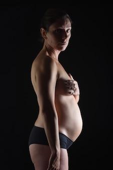 Portret van zwangere vrouw naakt kijken naar camera op zwarte achtergrond zes maanden