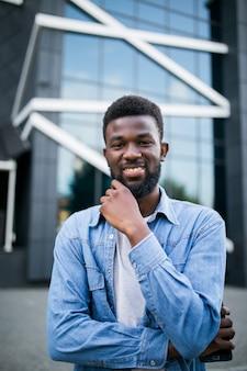 Portret van zwarte afrikaanse man erg blij, glimlachend in stedelijke achtergrond