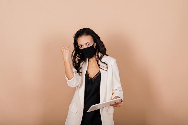 Portret van zwarte onderneemster die gezichtsmasker draagt tijdens virusepidemie in een studio.