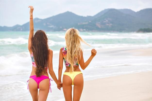 Portret vanaf de achterkant van mooi gebruinde meisjes met lang haar op het strand genietend van uitzicht op de bergen