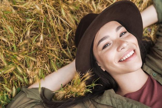 Portret vanaf de bovenkant van een jonge vrouw met lang donker haar met een elegante hoed die lacht terwijl ze buiten op het gras ligt