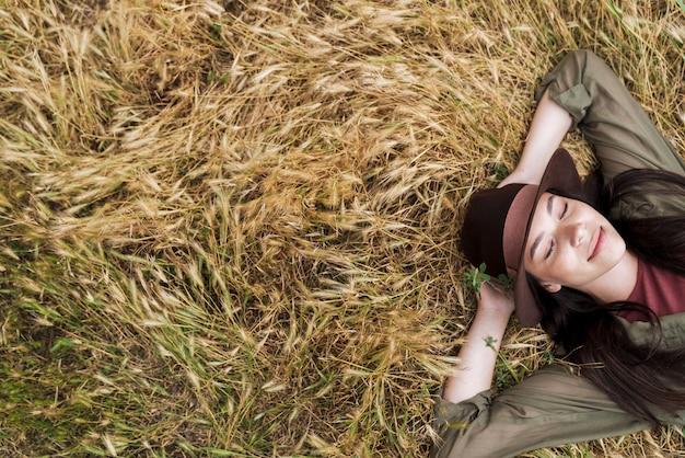 Portret vanaf de bovenkant van een ontspannen mooie vrouw met een hoed die ligt en rust met gesloten ogen in het veld buitenshuis