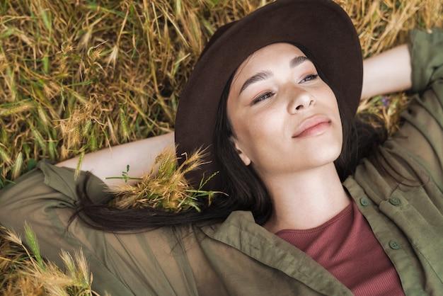 Portret vanaf de top van een mooie vrouw met lang donker haar met een elegante hoed die opzij kijkt terwijl ze buiten op het gras ligt