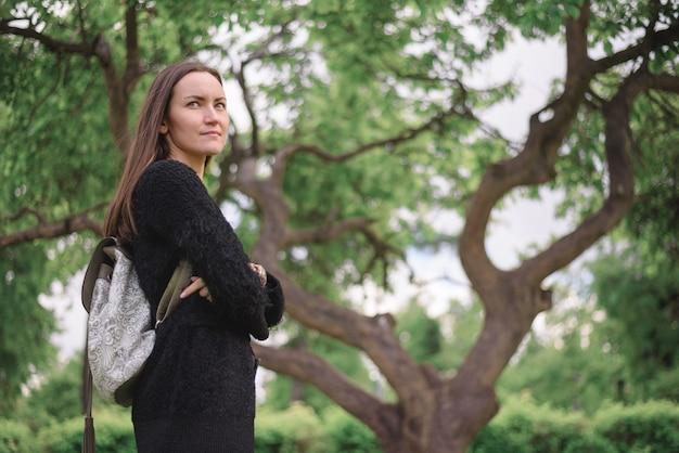 Portret vanuit de lagere hoek van een jonge vrouw met een donker zwart lang jasje en een lichte rugzak op de rug tegen een grote vertakte groene boom. kopie ruimte