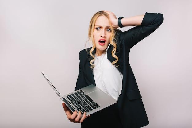 Portret verbaasde drukke jonge blonde vrouw die met laptop werkt. praten aan de telefoon, fout, overstuur humeur, te laat komen, kantoormedewerker, echte emoties