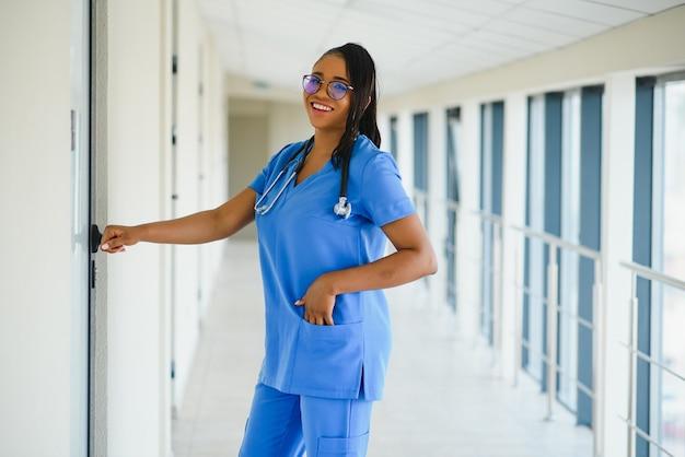 Portret vertrouwen afro-amerikaanse vrouwelijke arts medische professional schrijven patiënt notities geïsoleerd op ziekenhuis kliniek hal windows achtergrond. positieve gezichtsuitdrukking