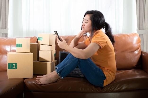 Portret verveelde jonge aziatische vrouw zit met behulp van een mobiele telefoon op de bank in haar kamer