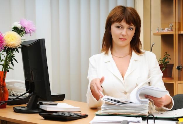 Portret volwassen glimlachende beautifu witte brunette vrouw met map met documenten zittend aan een bureau