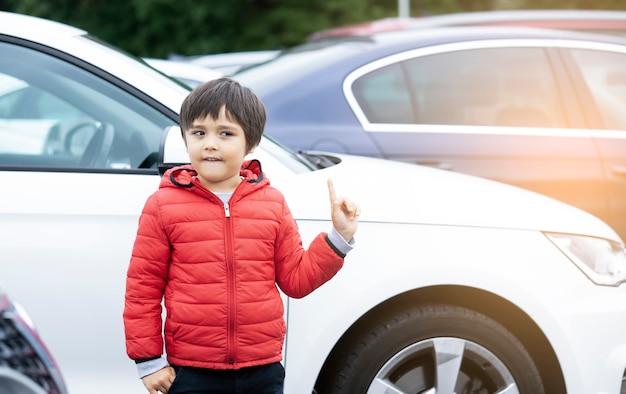 Portret voorschoolse jongen met een grappig gezicht staande naast de auto
