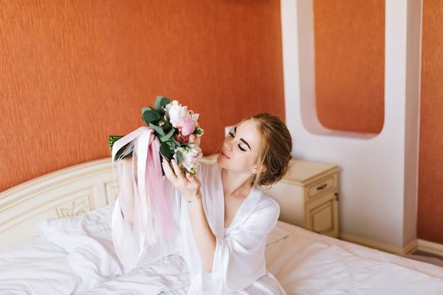 Portret vrij gelukkige bruid in witte badjas op bed in de ochtend. ze kijkt naar boeket in handen en ziet er blij uit