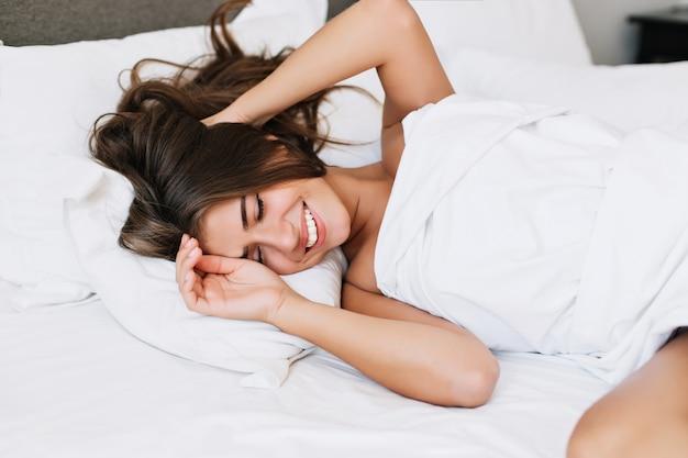 Portret vrij jong meisje op bed in modern appartement in de ochtend. ze houdt de ogen gesloten en ziet er tevreden uit.