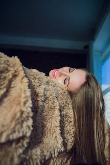 Portret vrij jong meisje op bed in moderne appartement in de ochtend
