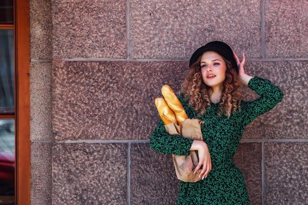 Portret vrij jonge vrouw met stokbrood in handen op de achtergrondstructuur van de muur. meisje gekleed in franse stijl toon emotie met brood. vrouw in stijlvolle kleding met verse baguettes. ruimte kopiëren