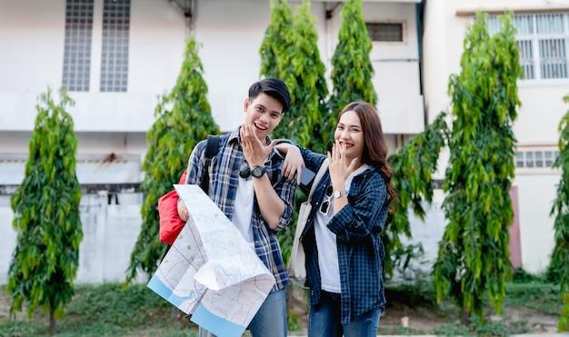 Portret vrolijk jong backpackerpaar glimlacht en lacht samen met gelukkig terwijl ze op straat in de stad reizen, knappe man met papieren kaart in de hand,