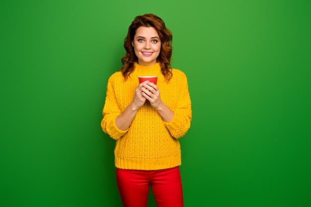 Portret vrolijke charmante mooie vrouw geniet van haar avondweekend vallen vrije tijd beker met hete aromatische cacao cappuccino draag goed kijken pullover geïsoleerde felle kleur muur