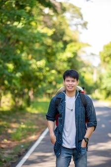 Portret vrolijke jonge man met rugzak die staat en lacht in het bospad, kopieer ruimte