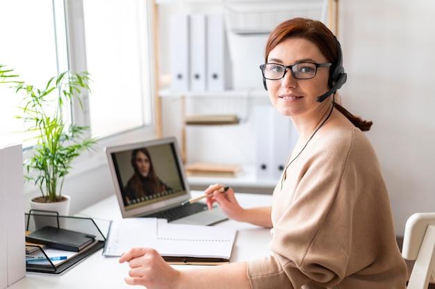 Portret vrouw aan het werk met video-oproep op laptop