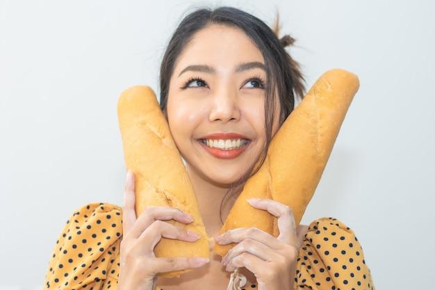 Portret vrouw blij met brood in broodwinkel, vrouwen met broodglimlach in bakkerijwinkel