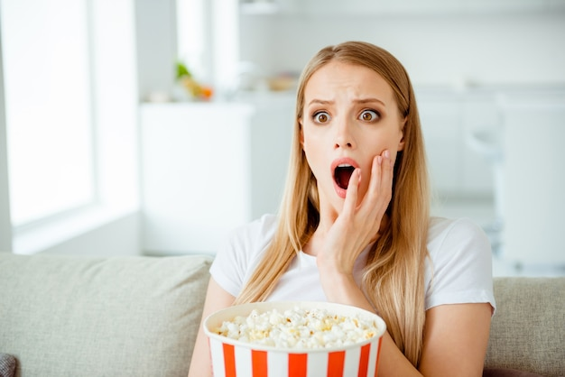 Portret vrouw die thuis popcorn eet