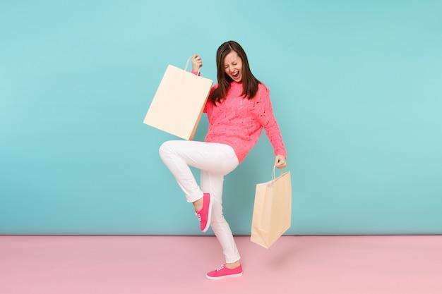 Portret vrouw in gebreide roze trui witte broek met veelkleurige pakketten tassen met aankopen