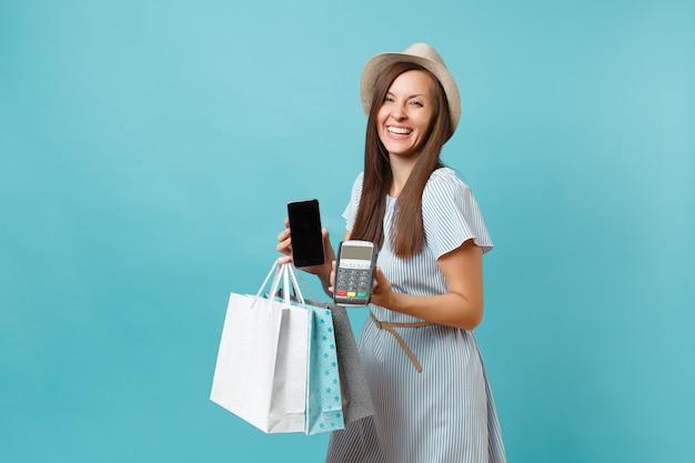 Portret vrouw in jurk, hoed met pakketten tassen met aankopen na het winkelen, draadloze moderne bankbetaalterminal voor het verwerken en verwerven van creditcardbetalingen geïsoleerd op blauwe pastelachtergrond.