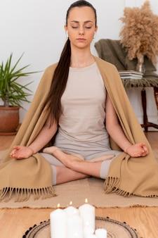 Portret vrouw mediteren met dienblad met kaarsen