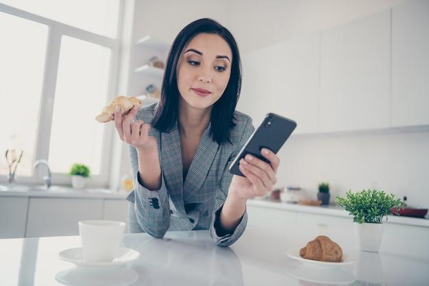 Portret vrouw met behulp van telefoon tijdens het ontbijt
