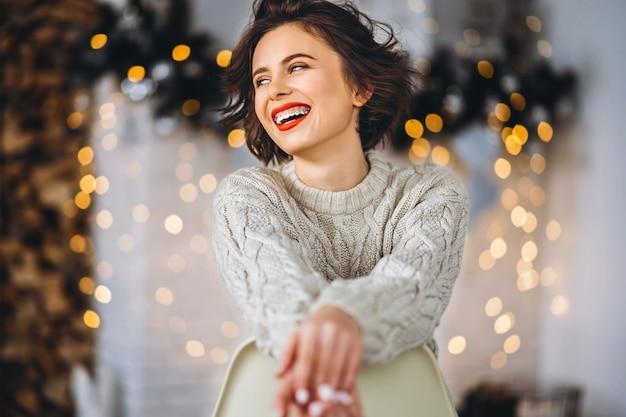 Portret vrouw zittend op de stoel in de buurt van de kerstboom