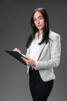 Portret vrouwelijke advocaat in formeel pak met klembord