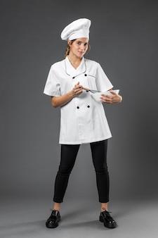 Portret vrouwelijke chef-kok met kom het mengen