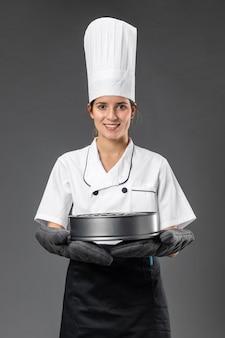 Portret vrouwelijke chef-kok met pan