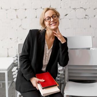 Portret vrouwelijke leraar met stapel boeken