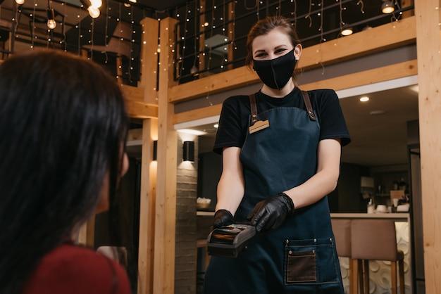 Portret vrouwelijke serveerster met een draadloze betaalterminal