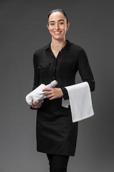 Portret vrouwelijke serveerster met fles wijn