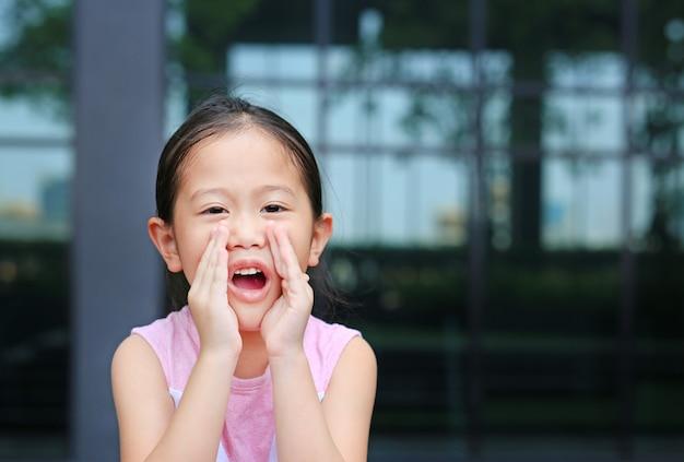 Portret weinig aziatisch kindmeisje die en door handen zoals megafoon handelen schreeuwen. communicatie concept.