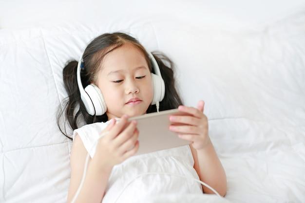 Portret weinig aziatisch meisje die hoofdtelefoons met een smartphone met behulp van