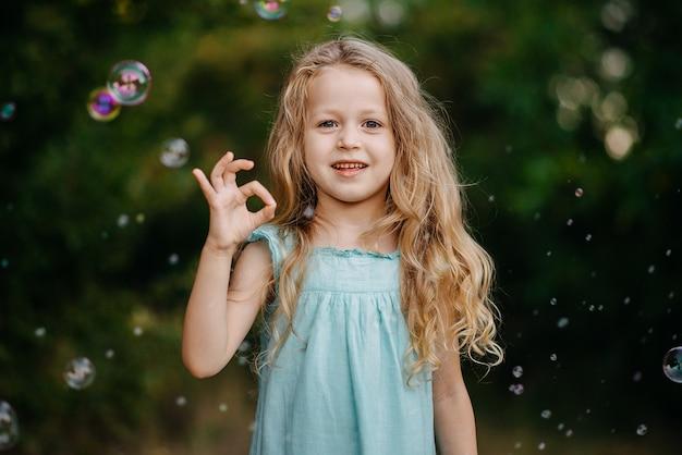 Portret weinig blond kind meisje vinger oke symbool gebarentaal tonen op groene natuur.