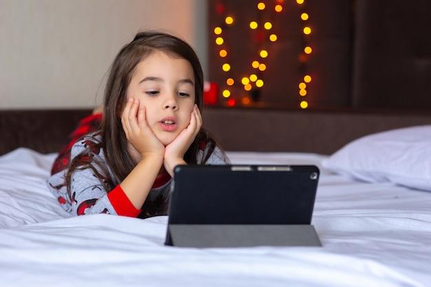Portret weinig brunette meisje, in rode en grijze pyjama's, ligt thuis op het bed