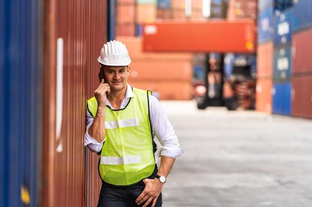 Portret werknemer ingenieur permanent met behulp van een mobiele telefoon en het controleren van het vak containers van vrachtschip naar export en import