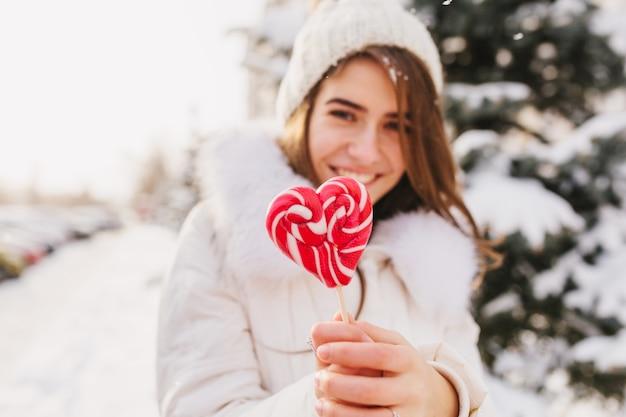 Portret winter jonge vrouw met roze hart lolly, chillen op straat vol met sneeuw in zonnige ochtend. witte gebreide muts, glimlachend.