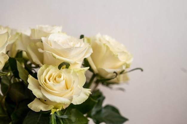 Portret wit frame mockup op houten tafel. moderne vaas met rozen. scandinavisch interieur. hoge kwaliteit foto