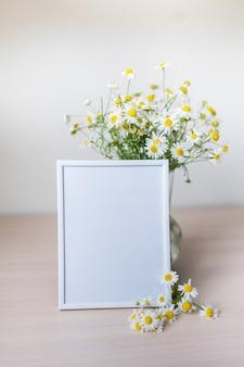 Portret witte fotolijst mockup op houten tafel glazen vaas met kamille
