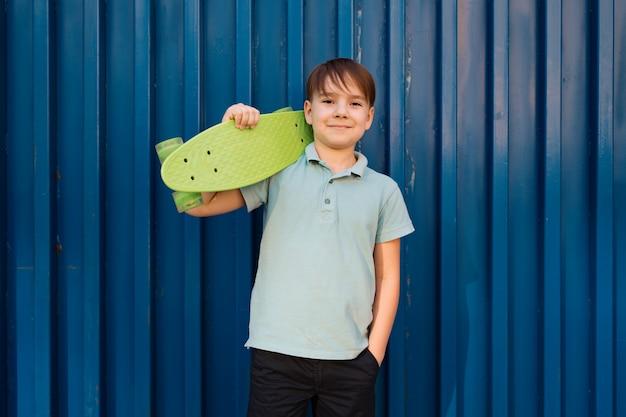 Portret young cool lachende jongen in blauwe polo poseren met skate op de schouder en hand in een zak