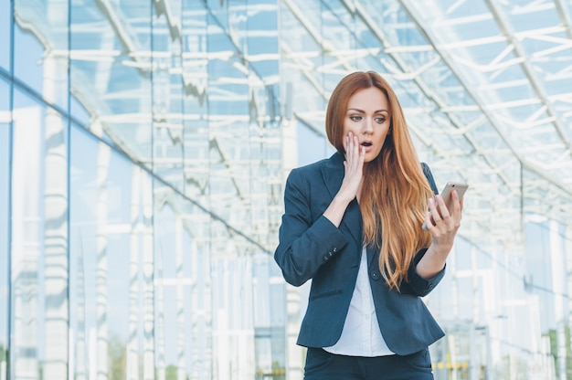 Portret zakenvrouw. op het gezicht verwondering kijken naar de telefoon in de hand gehouden.
