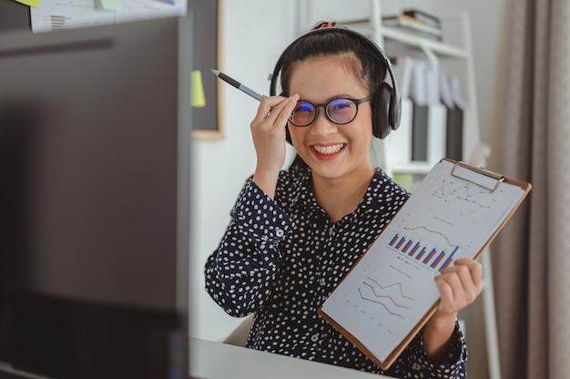 Portret zakenvrouwen met draadloze koptelefoon kijken naar computerscherm houden aangenaam