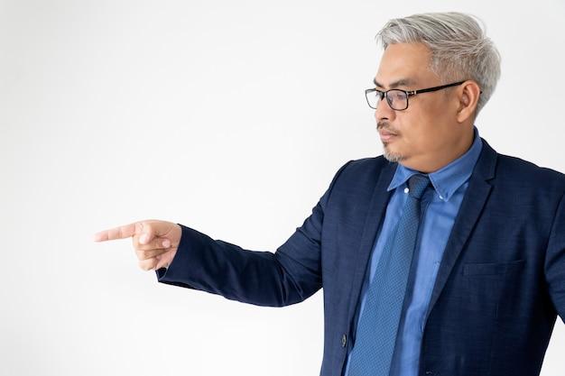 Portret zekere aziatische bedrijfsmens die glazen en blauw kostuum dragen die met hand op wit richten